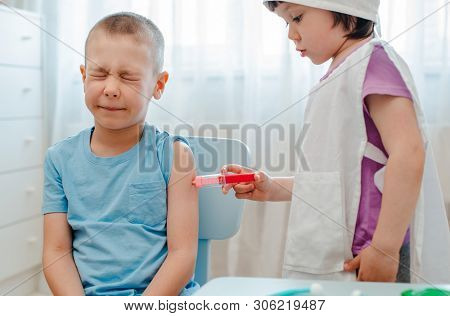 Children Play In The Hospital. The Girl Is Dressed In A Doctor 4 Years Old Makes An Injection To A B