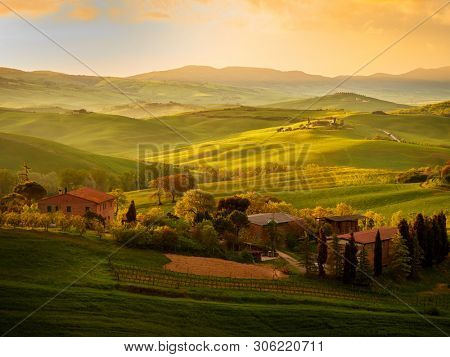 Amazing colorful sunset in Tuscany. Picturesque agrotourism and typical curved road with cypress, Crete Senesi rural landscape in Tuscany, Italy, Europe