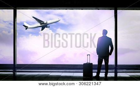 Man With Suitcase Looking Out At The Airport Window While Waiting For Flight Departure