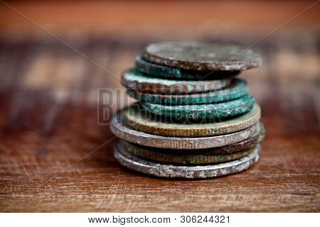 Stack of different ancient copper coins with patina on rustic wooden table background. With copy space.