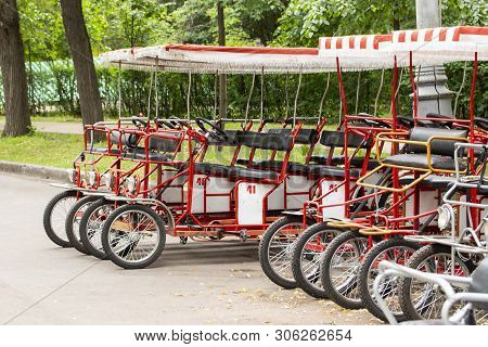 Red Cyclo Velomobiles With A Canopy For The Whole Family. Parked Rental Tourist Trike Vehicles. Ecol