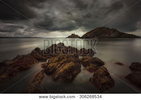 Dramatic Storm Clouds Over Swansea Bay And Mumbles Lighthouse In Swansea, South Wales Uk