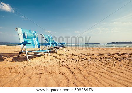 Two Blue Chaise-longues Are On The Sand Ocean Beach