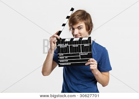 Casual young man holding a clapboard, over a gray background