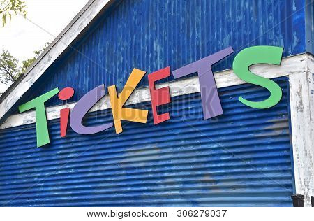 Colorful Letters Spell Out The Word T-i-c-k-e-t-s On The Side Of A Building At An Amusement Park.