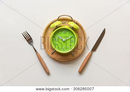 Diet And Weight Loss For Healthy Intermittent Fasting Lunchtime . Alarm Clock And Plate With Cutlery