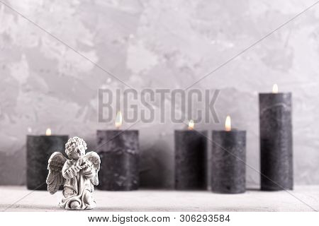 Mourning  Background. Little Angel And Burning  Black Candles On Grey Textured Background. Card For