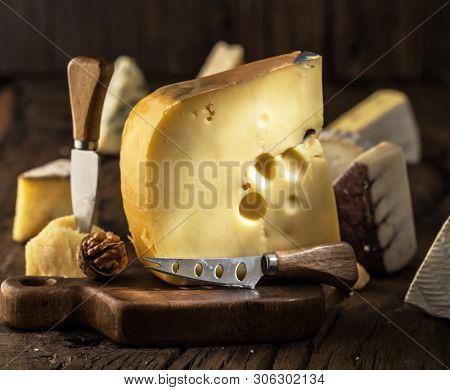 Piece of cow's milk Maasdam cheese on wooden board. Range of cheeses at the background.