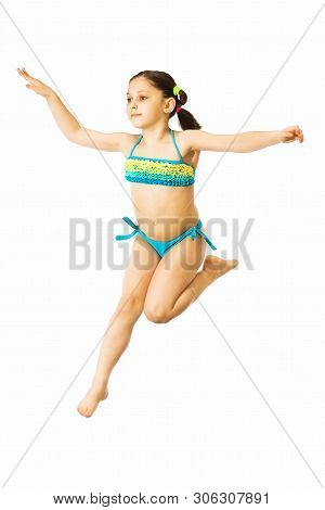Little Caucasian Female 8 Years Old Girl In Multicoloured Swimmwear Jumping On White Background.