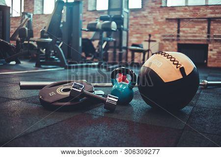 Disassembled Barbell, Medicine Ball, Kettlebell, Dumbbell Lying On Floor In Gym. Sports Equipment Fo