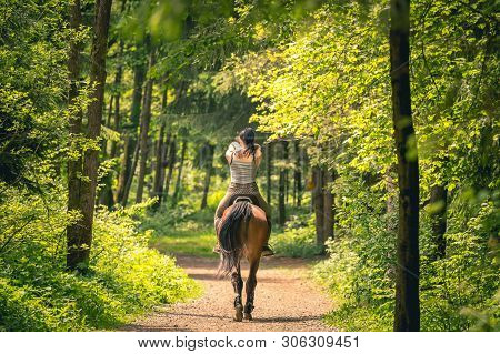 Beautiful Woman Riding A Horse In The Forrest, Soft Background, Shot Form Behind.