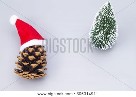 The Image Shows A Pine Crone With Santa Hats And A Model Tree, Isolated On Grey