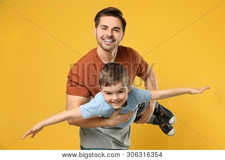 Portrait Of Dad Playing With His Son On Color Background