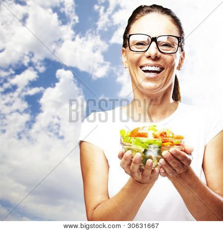 portrait of middle aged woman holding salad against a cloudy sky background