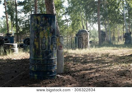 Iron Barrels In The Foreground With Multi-colored Blots And Smudges From Shots From The Paintball We