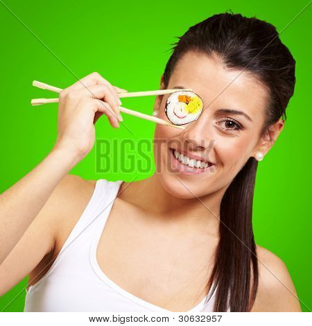 young woman covering her eye with a sushi piece against a green background