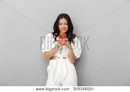 Attractive smiling young woman wearing summer outfit standing isolated over gray background, using mobile phone