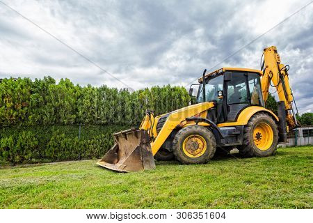 Bulldozer in the yard indicates the beginning of the construction of a new house