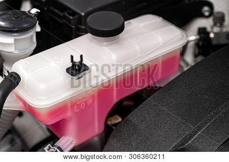 Close-up White Expansion Tank With Pink Antifreeze. Car Coolant Level In Radiator System In Car, Aut