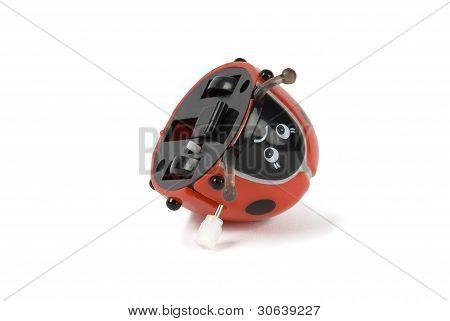Wind-up ladybird toy on its back on white background