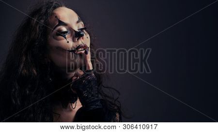 Makeup For Halloween. Sexy Brunette Girl In Black Clothes With A Scary Art On Her Face Keeps Her Ind