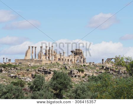 Great ruins of ancient Roman and african city of Volubilis in Morocco near Meknes with cloudy blue sky in 2019 warm sunny spring day on April. poster