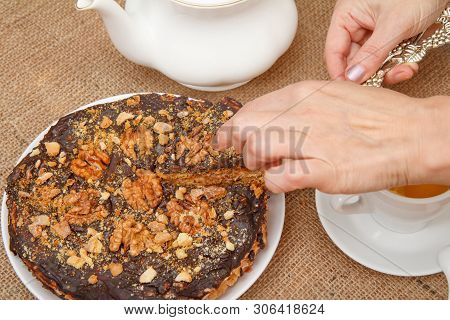 Female Hands Holding A Piece Of Homemade Chocolate Cake With Silver Cake Lifter And Cup Of Tea, Porc