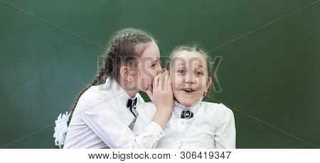 School Friend Tells A Secret In His Ear.school Friend Tells A Secret In His Ear. Schoolgirls Classma