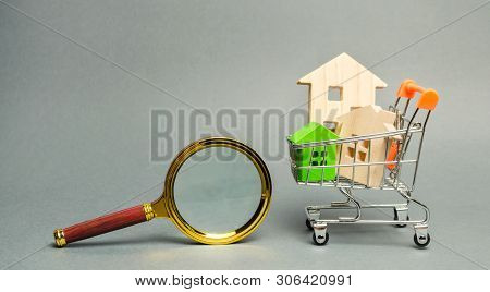 Magnifying glass and miniature wooden houses. House searching concept. Home appraisal. Property valuation. Choice of location for the construction. Search for housing and apartments. Real estate poster