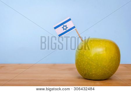 Granny Smith green apple grown in Israel with a little Israeli flag. Fruit made in Israel, Israeli fruits concept image. poster