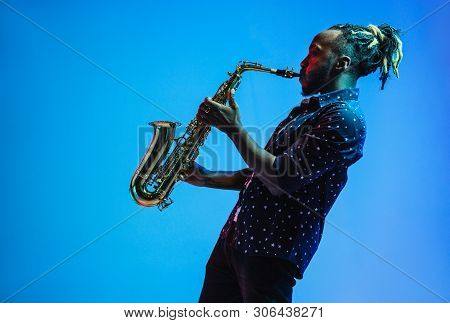 Young African-american Jazz Musician Playing The Saxophone On Blue Studio Background In Trendy Neon
