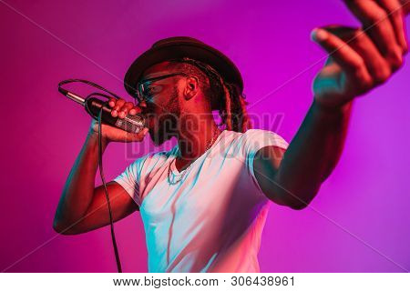 Young African-american Jazz Musician With Microphone Singing A Song On Purple Studio Background In T
