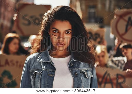 Women Power. Afro American Woman With Word Power Written On Her Face Protesting With Group Of Female