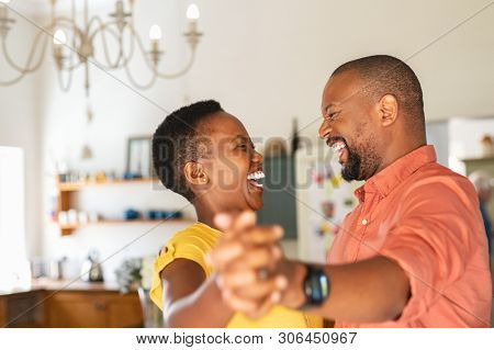 Cute mature couple dancing at home for their anniversary. Happy black woman enjoying a dance in the arms of her husband. Happy african couple dancing together in the kitchen and having fun together.