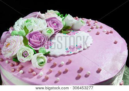 Biscuit Cake Layered With Mascarpone Cream And Berry Cream And Mastic Flowers On Dark