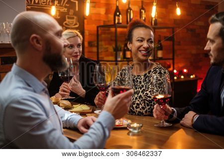 Group of friends having fun talk behind bar counter in a cafe