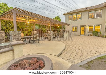 Patio With Dining Area And Built In Circular Benches Wrapped Around A Fire Pit