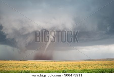 A Thin Cone Tornado Spins Over The Open Landscape Of The Great Plains.