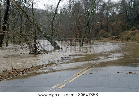 A River Floods Onto A Road Making It Hazardous And Impassable