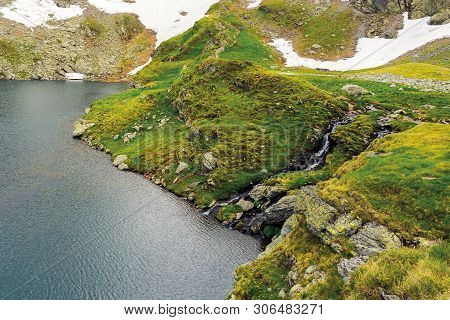 Glacier Mountain Lake In Summer. Beautiful Nature Scenery. Wonderful Background With Water, Grass, A