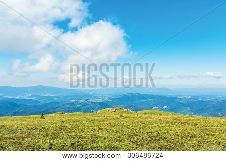 Beautiful Minimal Landscape. Fluffy Cloud Above Flat Grassy Meadow. Rocks On The Distant Hump. Mount