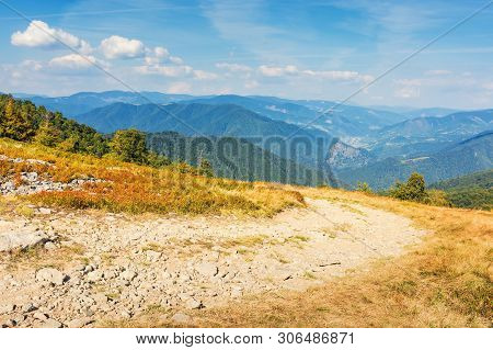 Gravel Road Through The Mountain Meadow.  Beautiful Summer Scenery With Clouds On A Blue Sky. Wonder