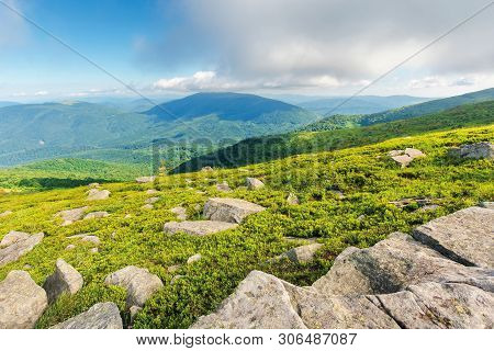 Rocks On The Grassy Hillside. Beautiful Landscape On Sunny Summer Morning. Low Fluffy Clouds Hang On