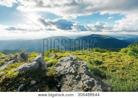 Rocks On The Grassy Mountains Meadow At Sunset. Wonderful Bright Summer Scenery. Beams Of Light Come