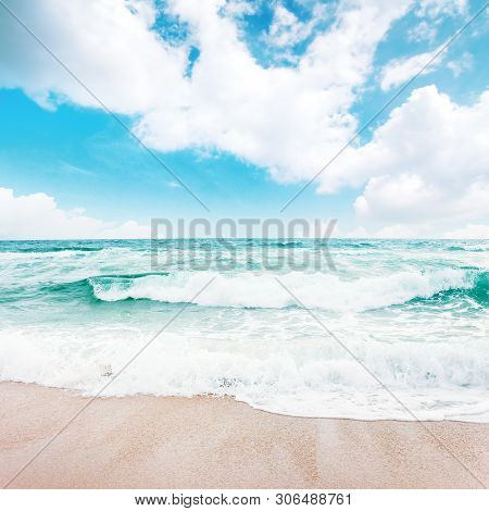 Sea Waves Crash On Sandy Beach. Wonderful Sunny Weather With Clouds On The Horizon. Emerald Water Be