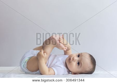 Little Hungry Baby Boy Taking Feet In Mouth. 6-month Baby Having Fun In White Bedding. Cute Baby Lyi