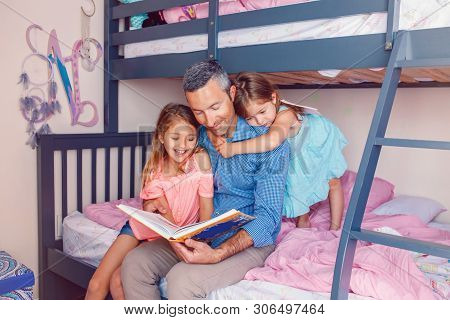 Family Of Three Members People Sitting On Bed In Bedroom Reading Book. Father And Daughters Girls At