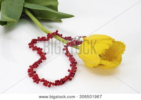 Bright Red Beads And Yellow Tulip With Green Leaves.