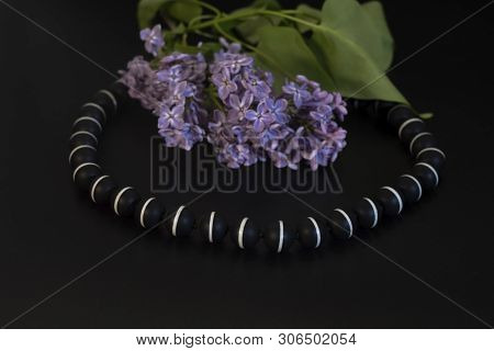 Bright Black Beads With A White Stripe And Lilac With Green Leaves.
