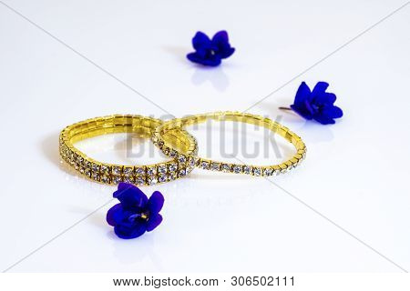 Two Brilliant Metallic Gold Bracelets And Blue Flowers.